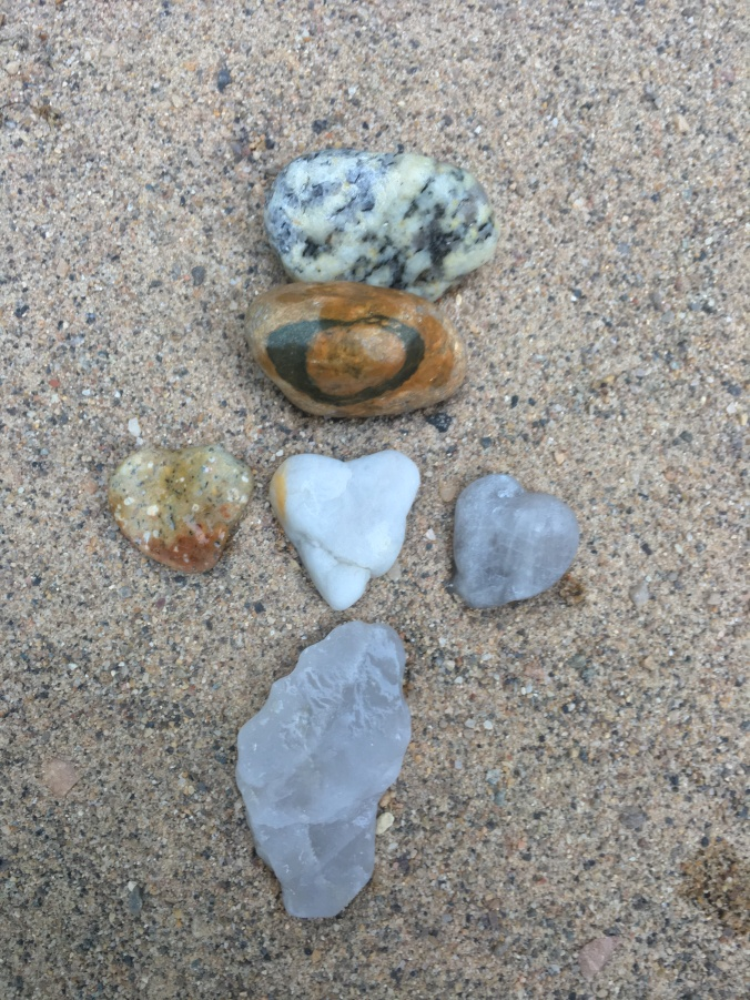 Three heart-shaped stones in the center, a stone with a heart ring above, and a footprint stone below.