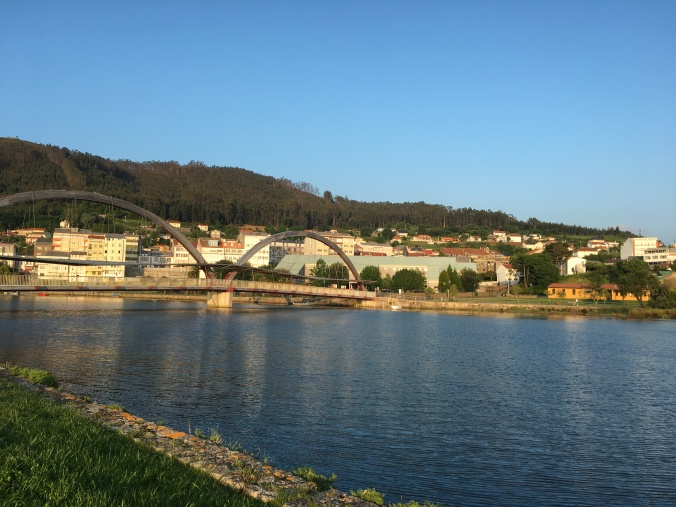 View of the footbridge with the orange municipal albergue on the right and Pension Maragoto on the left.